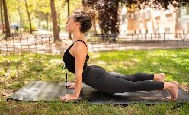Mulher fazendo ioga no parque