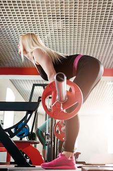 Mulher fazendo levantamento terra no ginásio