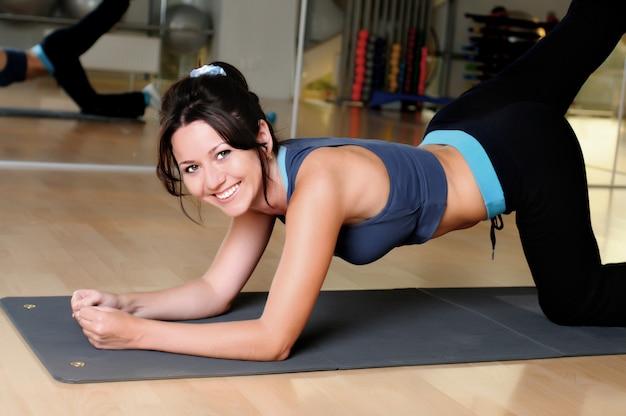 Mulher fazendo lunges físicos com halteres