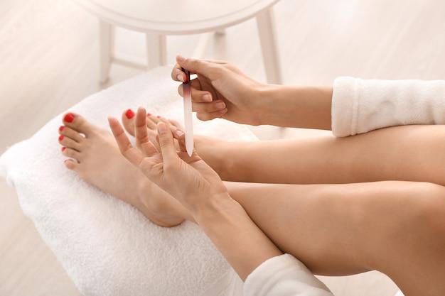 Mulher fazendo manicure em casa