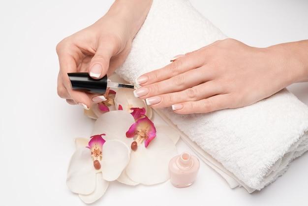 Mulher fazendo manicure sozinha em superfície cinza