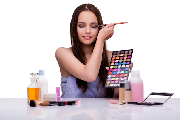 Mulher fazendo maquiagem em branco