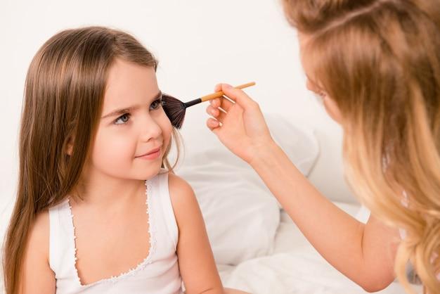 Mulher fazendo maquilagem para sua linda filha
