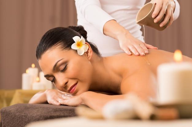 Mulher fazendo massagem com óleo nas costas