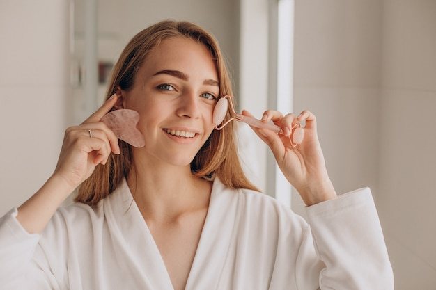 Mulher fazendo massagem com pedra gua sha e rolo facial