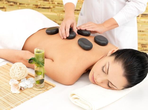Mulher fazendo massagem com pedras quentes nas costas no salão de beleza