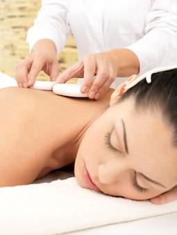 Mulher fazendo massagem com pedras quentes no corpo em salão de beleza