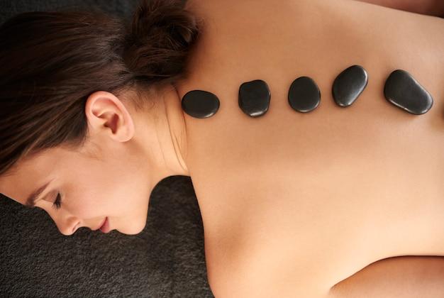 Mulher fazendo massagem com pedras quentes