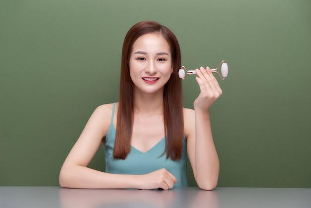 Mulher fazendo massagem com rolo de jade rosa. ferramentas de beleza para tratamento facial.