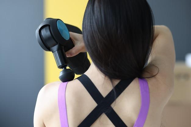 Mulher fazendo massagem nos músculos do pescoço e das costas com o massageador de percussão closeup
