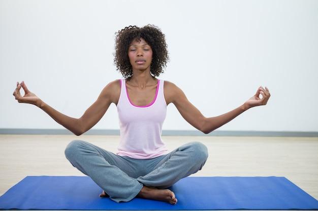 Mulher fazendo meditação no colchonete