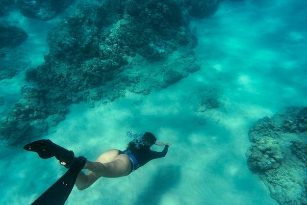 Mulher fazendo mergulho livre com nadadeiras debaixo d'água