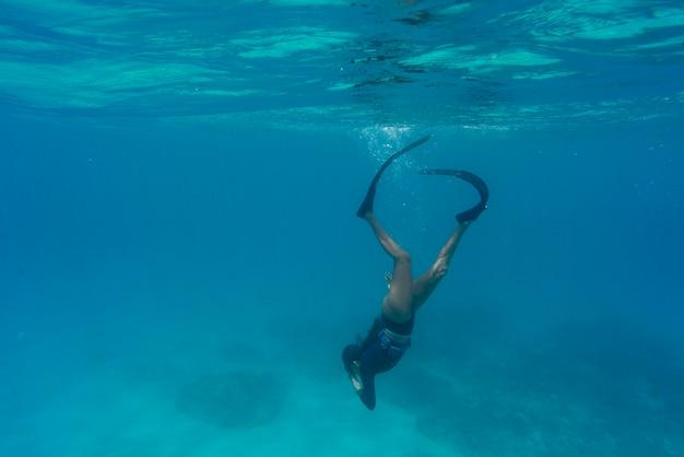 Mulher fazendo mergulho livre com nadadeiras debaixo d'água Foto gratuita