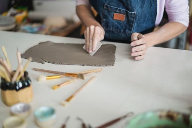 Mulher fazendo objetos de cerâmica dentro do estúdio de cerâmica criativa - conceito de arte e oficina - foco na mão direita