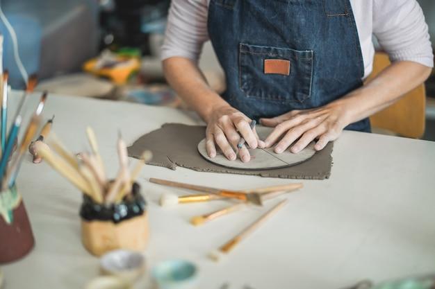 Mulher fazendo objetos de cerâmica dentro do estúdio de cerâmica criativa - conceito de arte e oficina - foco nas mãos