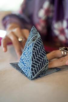 Mulher fazendo origami com papel japonês