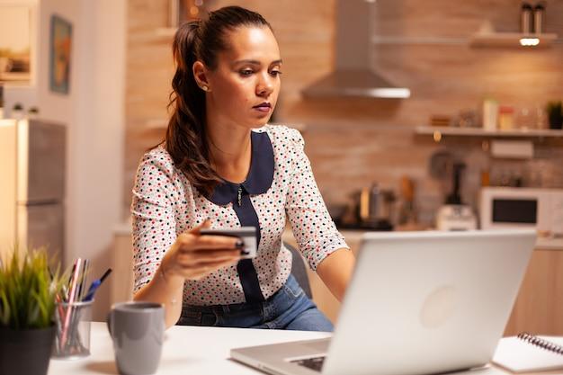 Mulher fazendo pagamento online na cozinha de casa tarde da noite, segurando o cartão de crédito. senhora criativa fazendo transações online usando notebook digital conectado à internet.