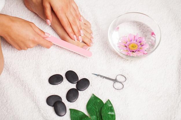 Mulher fazendo pedicure nos pés no apartamento