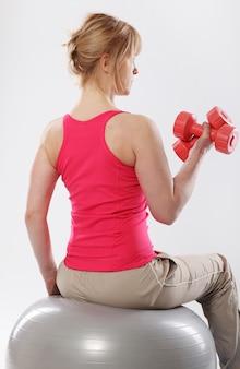 Mulher fazendo pilates e exercícios de equilíbrio com bola cinza