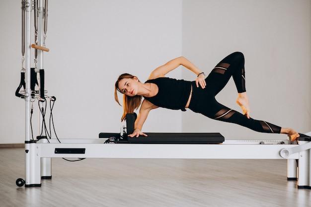 Mulher fazendo pilates em um reformador