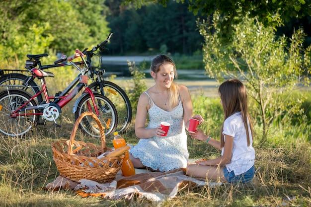 Mulher fazendo piquenique à beira do rio com a filha de 10 anos. duas bicicletas ao fundo