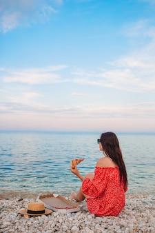 Mulher fazendo piquenique com pizza na praia
