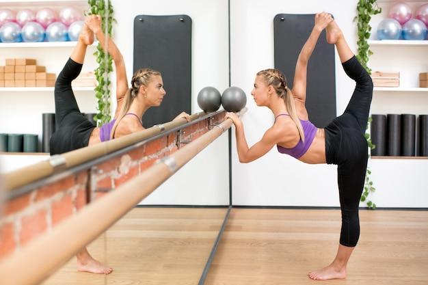Mulher fazendo pose de dança, mantendo a barra no ginásio