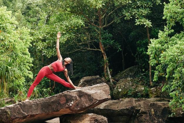 Mulher fazendo pose de triângulo