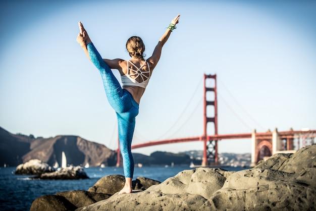 Mulher fazendo poses de ioga na praia.