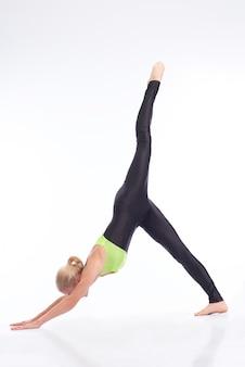 Mulher fazendo posição de cachorro virada para baixo com uma perna esticada no ar