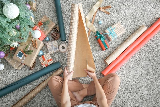 Mulher fazendo presente de natal no chão, vista de cima