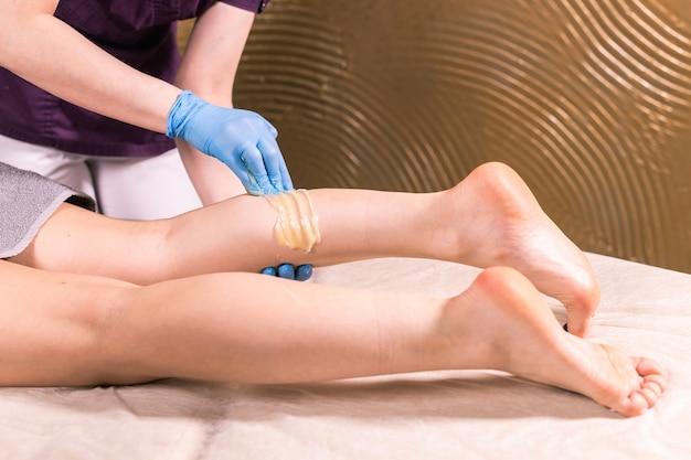 Mulher fazendo procedimento de depilação na perna com pasta de açúcar