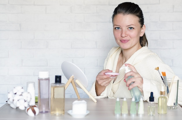 Mulher fazendo procedimentos de spa usando cosméticos naturais.