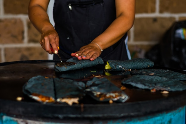 Mulher fazendo quesadillas mexicanas com milho azul e flor de abóbora.