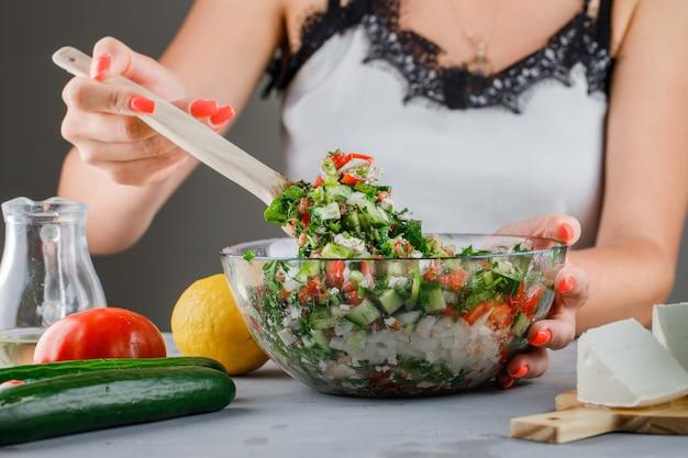 Mulher fazendo salada de legumes em uma tigela de vidro com tomate, queijo, pepino na superfície cinza