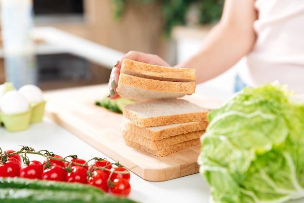 Mulher fazendo sanduíches com legumes em uma placa de corte