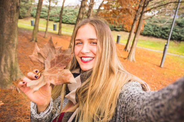 Mulher fazendo selfie com licença de outono