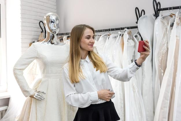 Mulher fazendo 'selfie' com manequim em loja de casamento