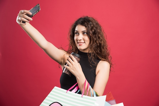 Mulher fazendo selfie com sacos e copo em fundo vermelho. foto de alta qualidade