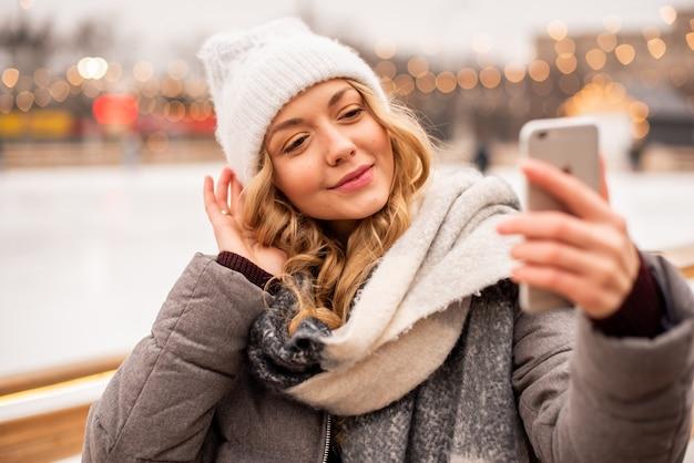 Mulher fazendo selfie no fundo do gelo festivo de natal. senhora vestindo roupas de malha quentes de inverno.