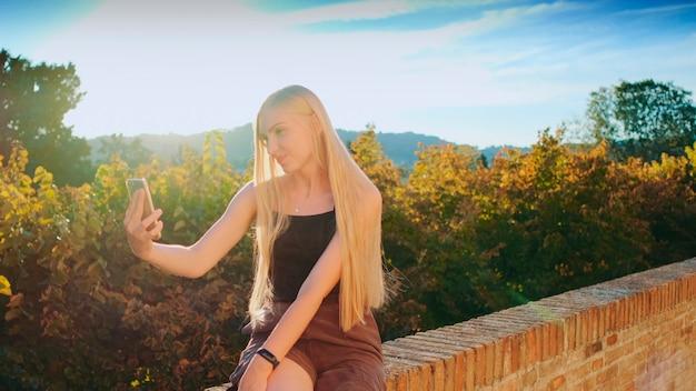 Mulher fazendo selfie no smartphone em frente a uma bela paisagem de natureza, viagem de verão para outro país
