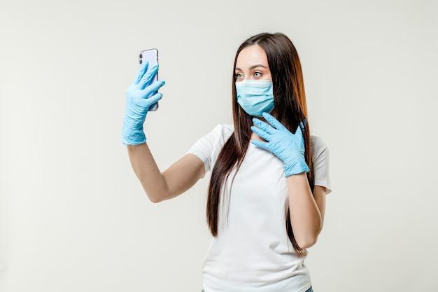 Mulher fazendo selfie usando luvas e máscara