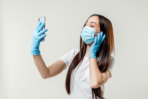 Mulher fazendo selfie usando máscara e luvas isoladas no fundo branco