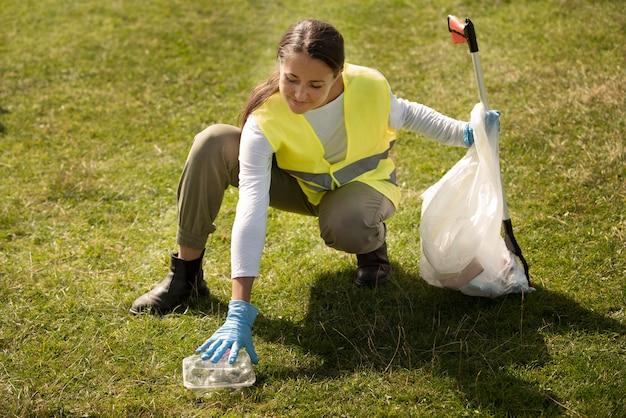 Mulher fazendo serviço comunitário ao coletar lixo