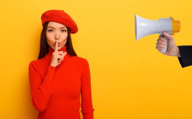 Mulher fazendo silêncio com o dedo no lábio ao lado de um megafone