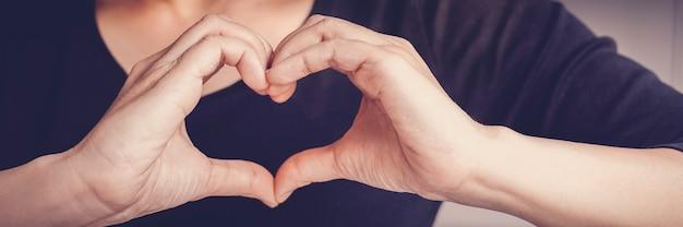 Mulher fazendo sinal de forma de coração com as mãos