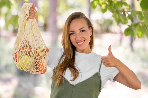 Mulher fazendo sinal de positivo ao lado de uma sacola biodegradável com guloseimas