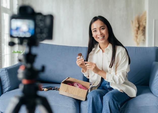 Mulher fazendo streaming ao vivo em casa com ferramentas de maquiagem