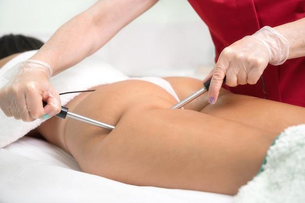 Mulher fazendo tratamento cosmético de beleza galvânica em terapeuta de spa aplicando corrente de baixa frequência