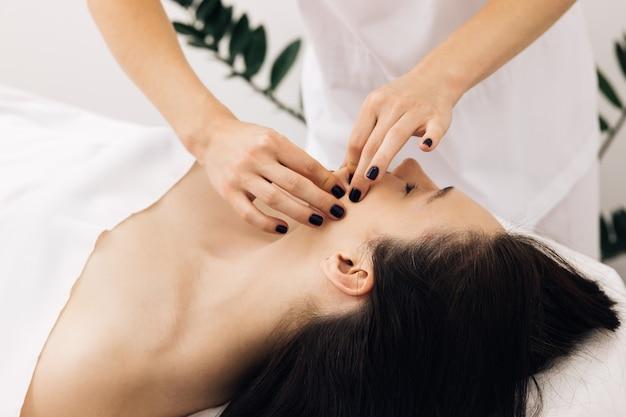 Mulher fazendo tratamento cosmético no salão de spa cosmetologista tocando rosto de meninas para limpeza facial